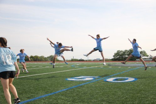 Junior boys attempt to do toe touches.