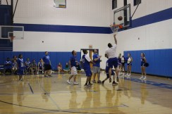 One of the Faculty members shooting a basket.