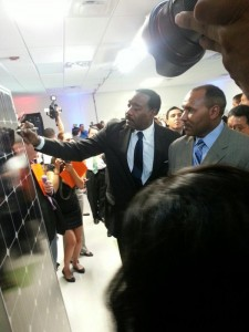 CPS Energy CEO Doyle Beneby signs a solar panel fresh off the line while Trustee Derrick Howard looks on.