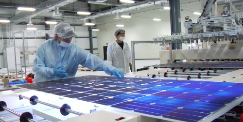 Mission Solar employee closely inspects each module for possible flaws.