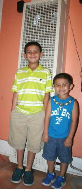 (Image) Troy, 9, and Isaiah, 4, pose in front of the wall furnace installed for free last winter through Casa Verde.