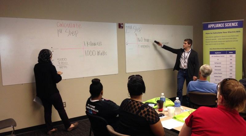 "(Image) Adam Bolin and Thuria Abdelaziz take teachers through a ""calculate your bill"" exercise. Intern Michael Saulnier developed the lesson for a curriculum."