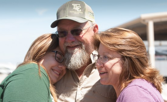 (Image) Will Schneider reunites with his family after helping restore electricity after Hurricane Harvey.