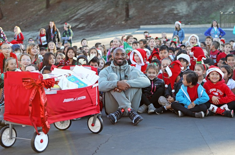 Kobe poses with students and books