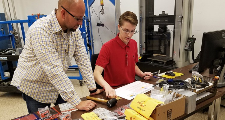 Laboratory technician Tony Figueroa helps El Toro High student Mason Maragon work design an experiment to test the integrity of a pad lock.