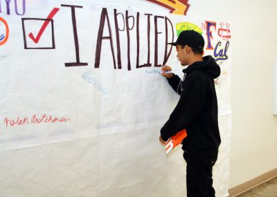 "Student signing a banner that reads, ""I applied."""