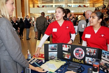 students show off their work to attendee at OC Pathways Showcase