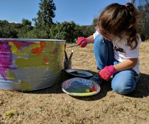 A young girl paints a metal pail.