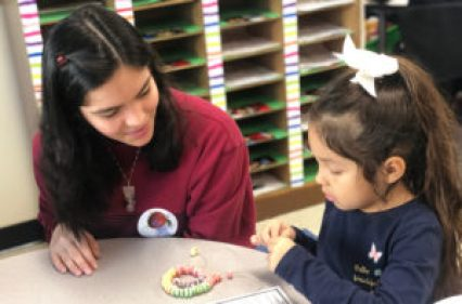 volunteer works with student at desk
