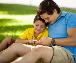 Father and son using cell phone