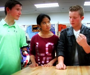An image of Tustin High juniors working on a prosthetic arm for a seventh-grade student
