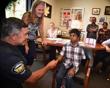 Tustin Police Officer Ralph Casiello and school nurse Pam Atkins greet Siva Pelluru.