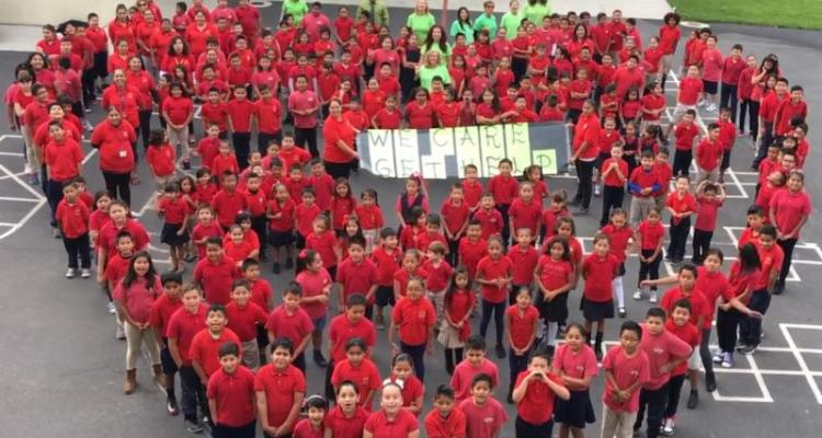 a group of students dressed in red form a heart on a school's blacktop