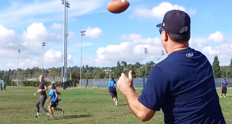 coach tosses a football to student athlete