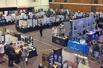 students exhibit projects inside a gymnasium