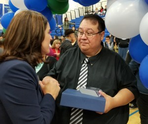 high school counselor receives congratulations at ceremony