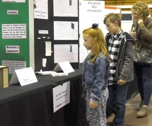 students and a parent view exhibits and science fair