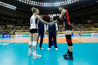 Volleyball players from the U.S. and Japan greet before a match
