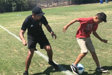 student and coach playing soccer