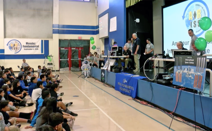 students on stage asking questions via audio stream to astronaut