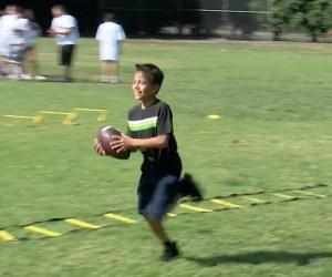 students runs across field carrying football