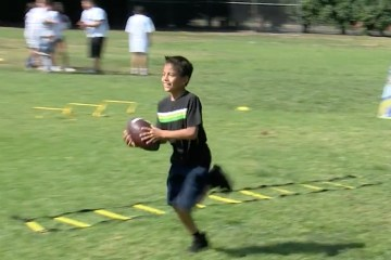 students runs across field carrying football