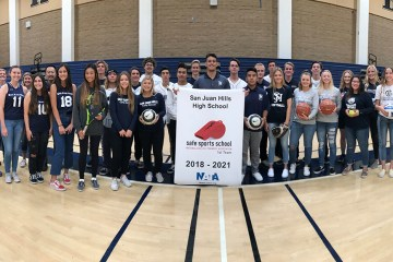 student athletes and staff from San Juan Hills High pose inside the school gym