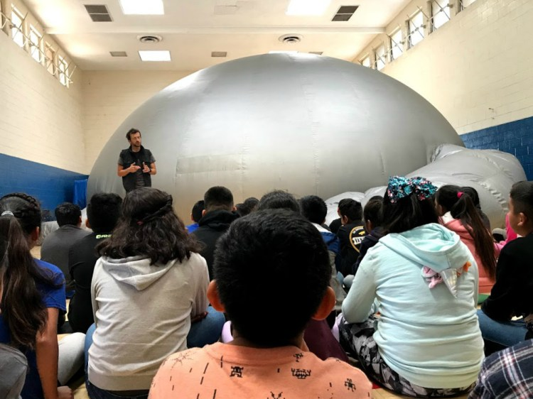 Students sitting in front of the inflatable SkyDome Planetarium