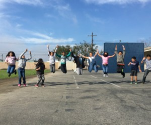 Elementary students on a playground jumping in the air