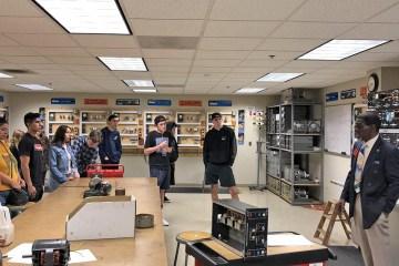 students stand inside classroom around a teacher