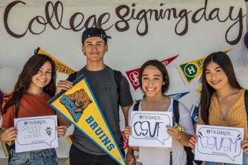 students hold up college banners