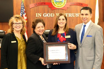Dr. Sonia Llamas, assistant superintendent in the Santa Ana Unified School District, holds her award