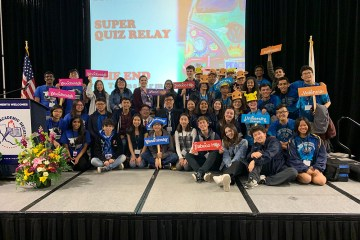 students from five high school academic decathlon teams pose for a photo on a stage