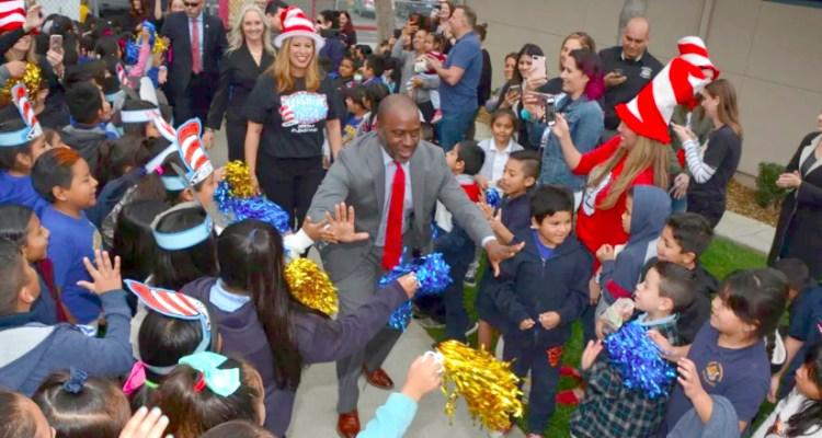 State Superintendent Tony Thurmond high-fives children