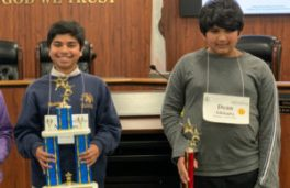 Two students hold up trophies