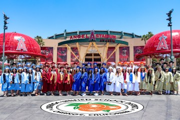 high school grads pose in front of angel stadium