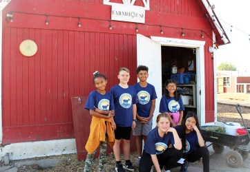 students pose in front of a barn