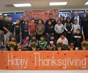 "Students in front of a ""Happy Thanksgiving"" sign"