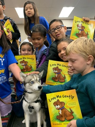 Students with books petting a dog