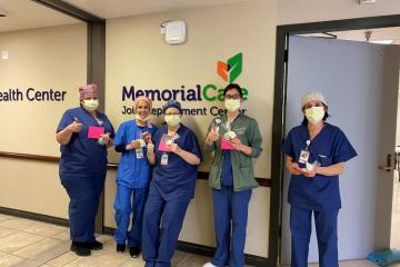Healthcare workers holding thank-you cards