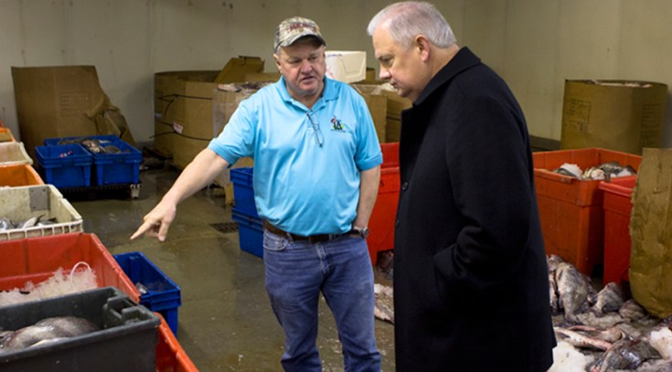 Newsroom Ink's vice president of strategic communication, Springfield Lewis (r), interviews LA Fish owner and former Seafood Board chair Harlon Pearce in the processing room. Photo: Ed Lallo/Louisiana Seafood News