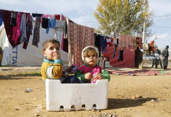 Syrian refugee children sit in a box at a makeshift settlement in Qab Elias in the Bekaa | Source: REUTERS/Mohamed Azakir