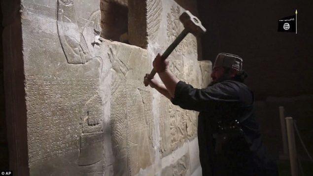 Атака: ISIS боевик использует кувалду, чтобы уничтожить несколько тысяч лет каменную плиту в видео якобы показывая нападение группы на древних руинах города Нимруде, недалеко от Мосула, Ирак