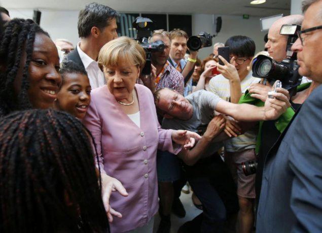 Канцлер Германии Ангела Меркель приветствует посетителей в течение дня открытых дверей в Штаб-квартира в Христианско-демократического союза (ХДС) в Берлине, Германия 4 июля 2015 REUTERS / Hannibal Hanschke TPX ФОТО ДНЯ