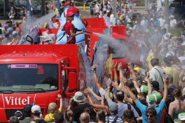 Автоприцеп рекламы распыляет воду на зрителей, поскольку они ждут начала первой стадии гонки езды на велосипеде Тур де Франс, отдельные гонки на время более чем 13.8 километров (8.57 миль), с началом и Концом в Утрехте, Нидерланды, суббота, 4 июля 2015. Температура повысились до 36 градусов Цельсия или 97 градусов по Фаренгейту около полудня. (AP Photo/Christophe Эна)