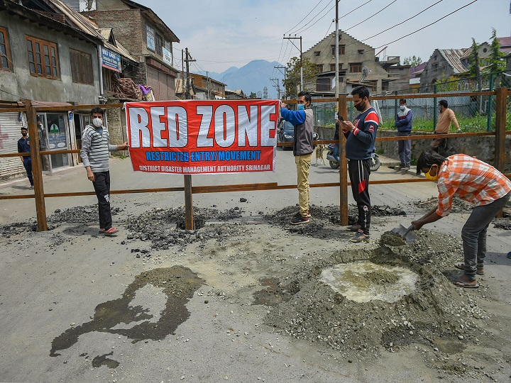 Srinagar: Workers place  a banner after erecting a road blockade at an identified red zone area for COVID-19 during a nationwide lockdown in the wake of coronavirus pandemic, in Srinagar, Tuesday, April 14, 2020. (PTI Photo/S. Irfan)(PTI14-04-2020_000137B)