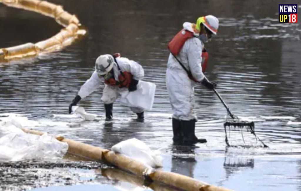 Workers in protective suits clean after oil spill from an offshore oil platform in California