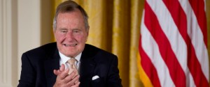 """Former President George H. W. Bush applauds as he participated in a ceremony to  present the 5,000th Daily Point of Light Award to Floyd Hammer and Kathy Hamilton, a retired couple and farm owners from Union, Iowa, in the East Room of the White House in Washington, Monday, July 15, 2013. Obama welcomed Bush to the White House in a salute to public service and to the drive for volunteerism that the 41st president inspired with his """"thousand points of light"""" initiative more than two decades ago.  (AP Photo/Carolyn Kaster)"""