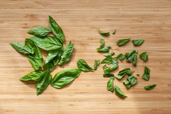 How to Make Caprese Pasta Salad - torn basil on a cutting board