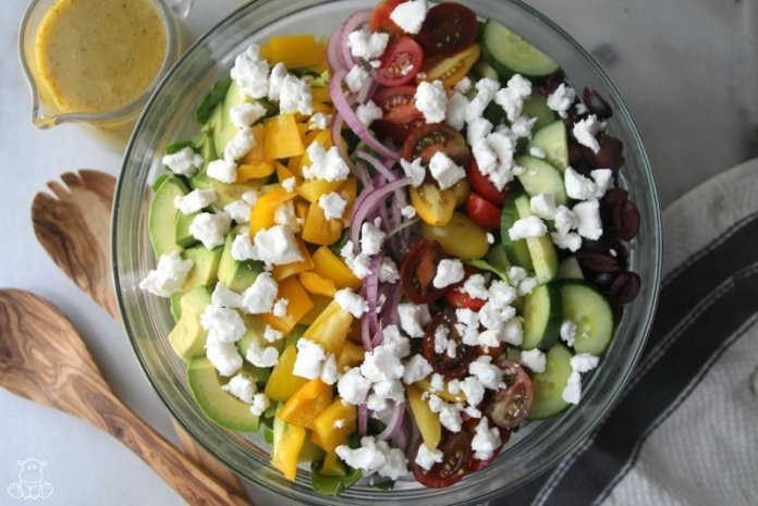 Greek salad in a bowl with dressing next to it